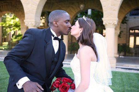 A young and attractive man and woman wedding couple kissing outside church photo