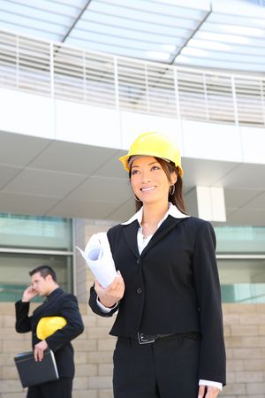 asian architect: A man and woman architect on a construction site working Stock Photo