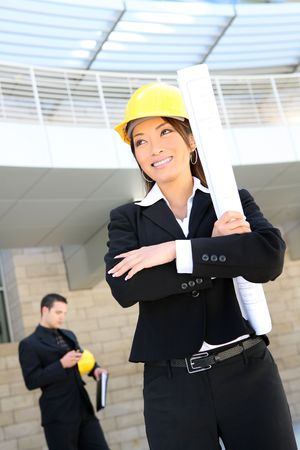 asian architect: A  woman architect on a construction site working with co-worker in background Stock Photo