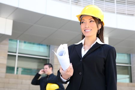 A  woman architect on a construction site working with co-worker in background photo