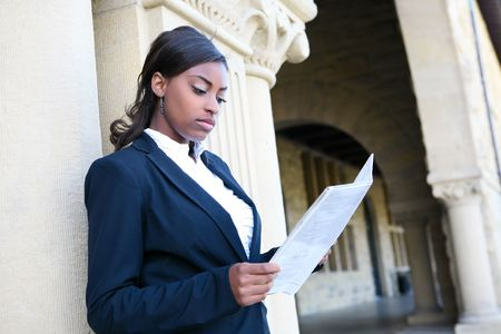 A young and pretty african american woman at college reading newspaper Stock Photo - 5999489