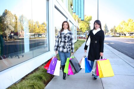 sales person: Pretty women shopping with colorful bags walking to the next store