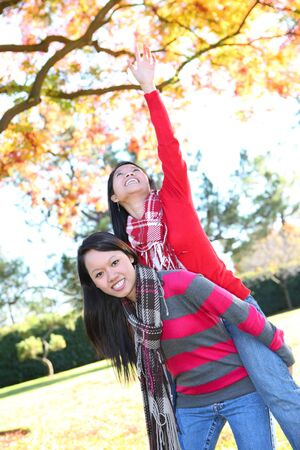 Pretty young asian girls in the park during autumn Stock Photo - 6048913