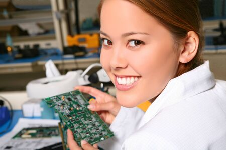 Pretty women technician working on computer parts in the lab
