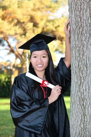 Pretty Asian woman wearing cap and gown holding diploma at graduation Stock Photo - 6076539