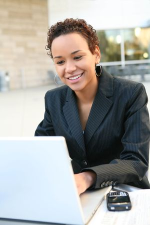 A pretty african american business woman on computer at office Stock Photo - 6076544