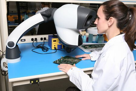 A pretty woman computer technician examining a printed circuit board with a microscope