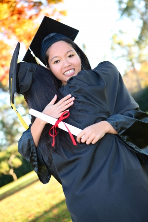 Pretty Asian woman wearing cap and gown holding diploma at graduation hugging friend