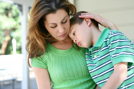 A cute tired boy and his mother on the porch at home showing love Stock Photo - 6099016