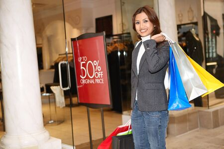 shopper: A pretty asian woman holding sale bags shopping in the mall