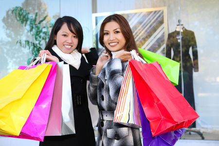Pretty women shopping with colorful bags walking to the next store photo