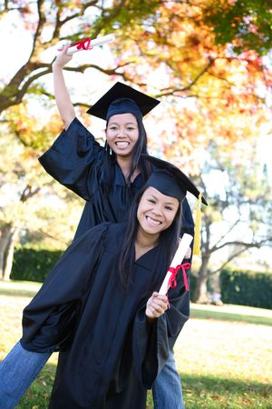 Pretty Asian woman wearing cap and gown holding diploma at graduation piggyback photo