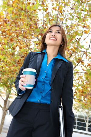 A pretty asian business woman walking with coffee Stock Photo - 6121486
