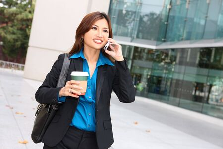 A pretty asian business woman walking with coffee talking on phone photo