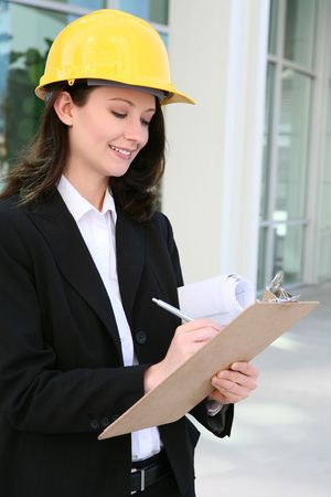 A pretty woman architect holding blueprints and writing on clipboard photo