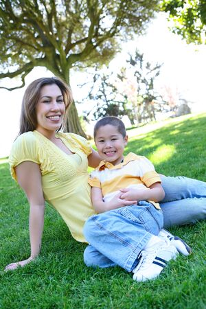 A cute and pretty mother and son laying on grass in the park photo