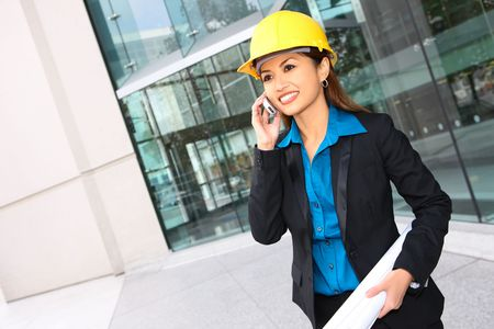 asian architect: A pretty asian architect woman at building site on phone