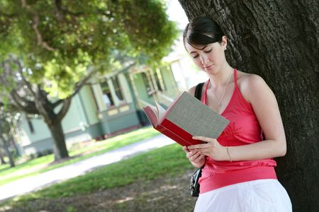A cute young girl reading a book under tree outside home photo
