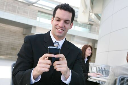 A handsome young business man texting on his phone at office building photo