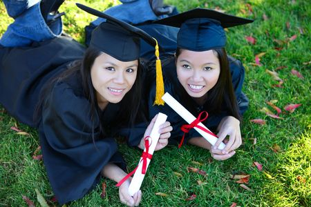 Pretty Asian women wearing cap and gown holding diploma at graduation photo
