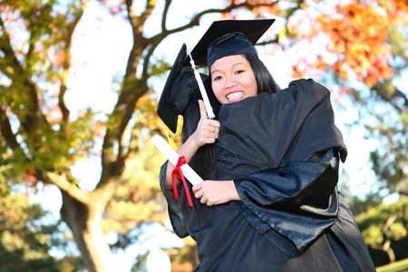 Pretty Asian woman wearing cap and gown holding diploma at graduation hugging friend photo