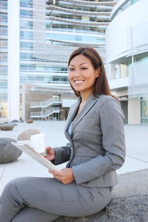 A young asian business woman reading the newspaper at office building photo