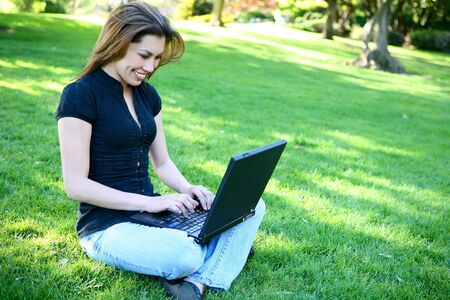 A pretty young woman student on laptop computer in grass in park