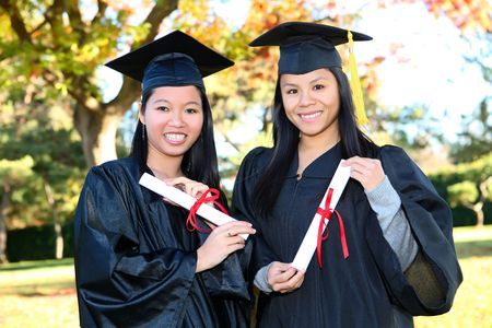 Pretty Asian woman wearing cap and gown holding diploma at graduation  photo