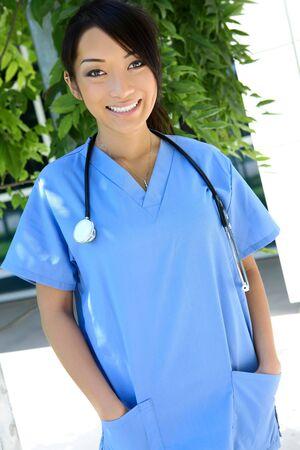 A cute young asian nurse outside the hospital photo