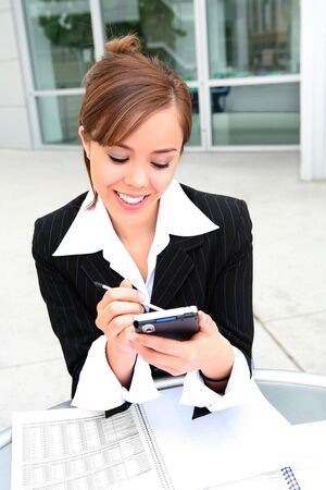A beautiful young business woman on laptop at office building photo