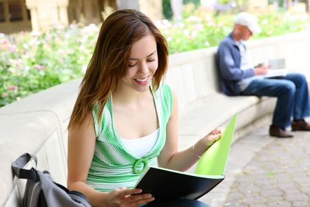 A pretty young woman reading on a bench at college photo