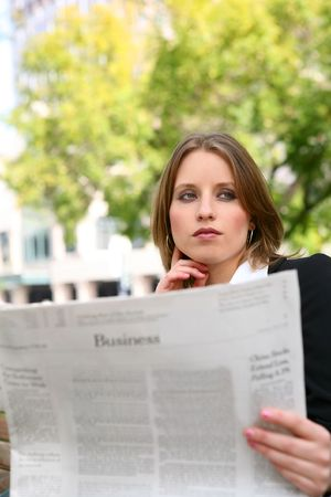 A young petty business woman reading the newspaper photo