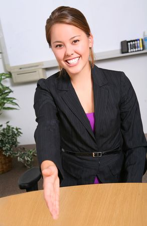 A pretty natural business woman in office offering a handshake Imagens