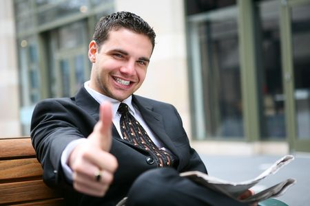 Handsome young business man giving thumbs p, outside office building photo