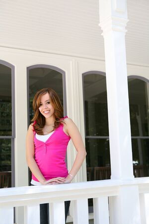A pretty young teen girl happy at home on the porch photo