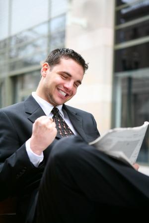 Succesvolle zaken man lezen van papier en vieren op kantoor gebouw