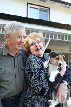 An upbeat joyful elderly man and woman couple in love at home with dog photo