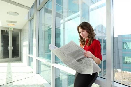 사무실 건물에서 신문을 읽는 젊은 매력적인 비즈니스 여자