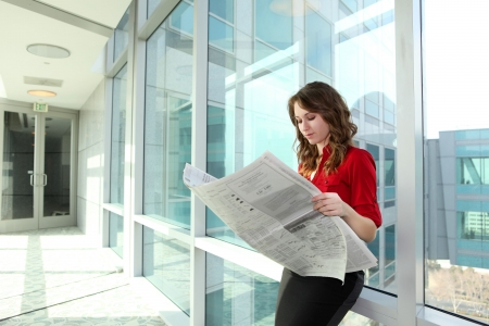 smart investing: A young attractive business woman reading newspaper at office building