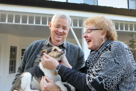 An upbeat joyful elderly man and woman couple in love at home with dog