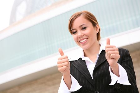 A pretty, young business woman with her thumb up showing success photo