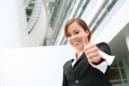 A pretty, young business woman with her thumb up signaling success photo