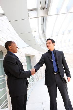 year profile: An attractive, diverse business man team shaking hands at office building