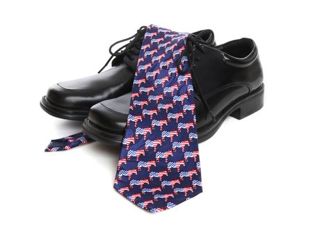 A business mans shoes and a democrat theme tie over white background photo