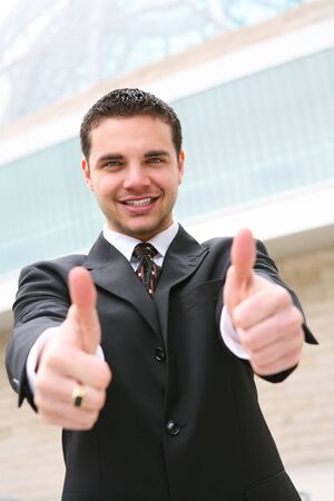 A handsome business man showing success with thumbs up at office building photo