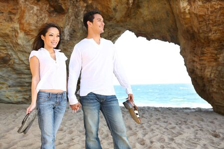Happy diverse attractive man and woman couple walking on the beach in love 版權商用圖片