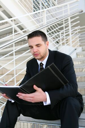 A young handsome business man reading at the office photo
