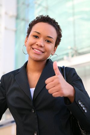 A pretty african american business woman with thumbs up at office building photo