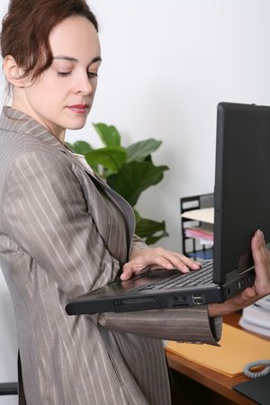 A pretty business woman in the office holding laptop computer photo