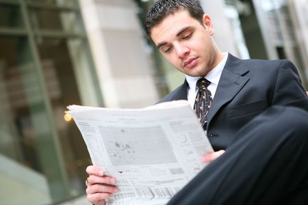 A handsome young business man reading the newspaper at office building photo